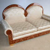 Double back sofas with sprung seats. Upholstered arched backs within mahogany frames richly decorated with inlaid marquetry. upholstered scroll arms and seat, faced with mahogany panels with matching inlays. Supported by bracket feet with beaten brass inlaid panels.