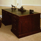 H.62 Mahogany Partner's Desk 72 inches x 48 inches x 30 inches H. Comprising eleven drawers, two cupboards and a deep file drawer. The top is divided into three sections by cross-bandings. Insert hide liners in your choice of colour and gold tooled.