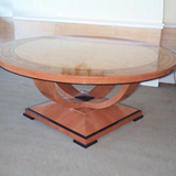 An Art Deco table 72 in diameter. The top is in Quilted Maple and Swiss Pear with a cross-banded in Mahogany and Ebony inlays. Raised from a pear four armed base also outlined in Ebony.