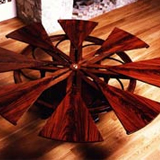 Jupe Table, made in three different sizes, when the apron is rotated the arms throw out the 'pie' leaves on glides to allow parallel leaf inserts, thus forming a larger circle.