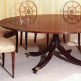 T.88 A Mahogany 'Segment' table with a centre diameter of 60 inches extending up to 76 inches diameter. Supported by a four splay pedestal base. C.16 chairs. T.88 BOX. A Mahogany storage box can be supplied for the crescents, which is baize lined.